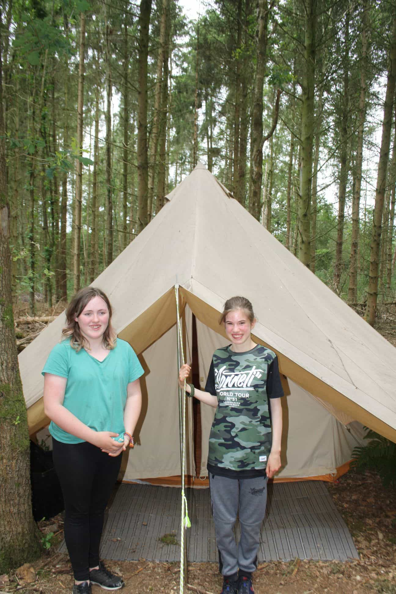Niamh and Lauren show off their tent on LVS Oxford's residential trip to Blenheim Woods