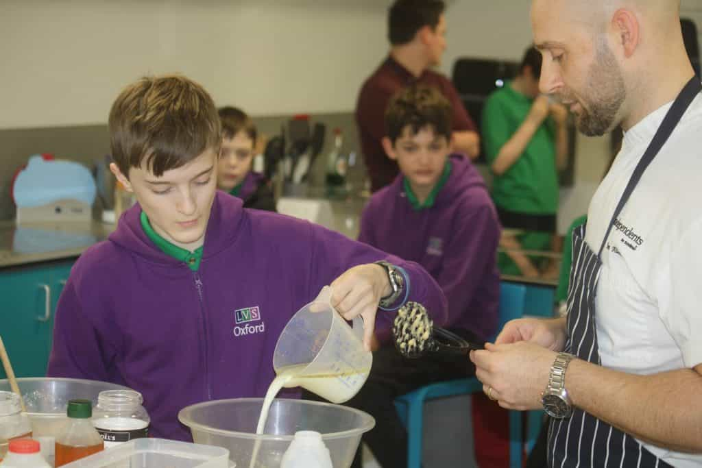 chef watches on as pupil pours egg mix into bowl
